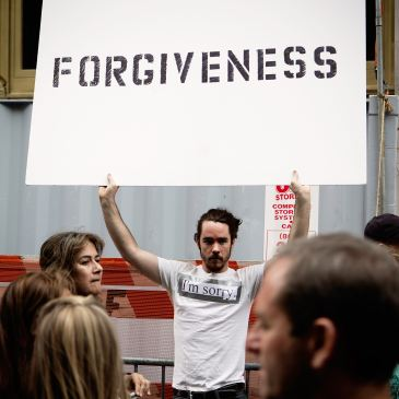 Man holds forgiveness sign